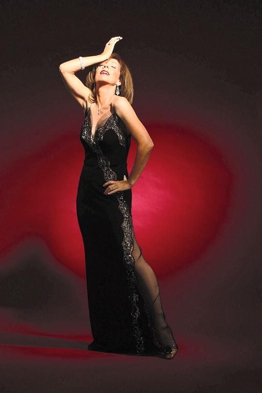 Rita Rudner standing in ballgown hand to head