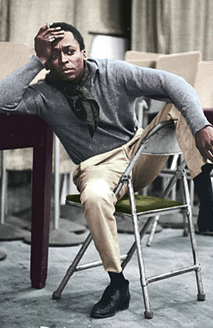 Miles Davis thinking on chair leg draped